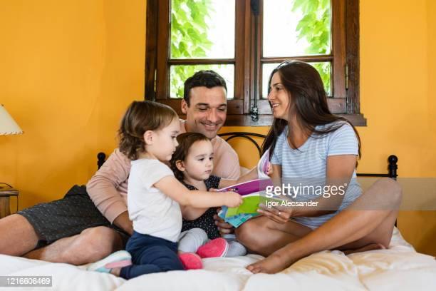 ベッドでの双子の子供を持つ家族 - 南アメリカ ストックフォトと画像