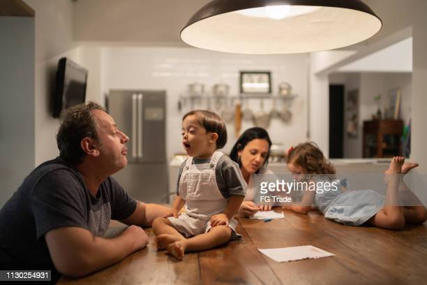 Family with twin sibling (Down Syndrome Boy and Girl) at table