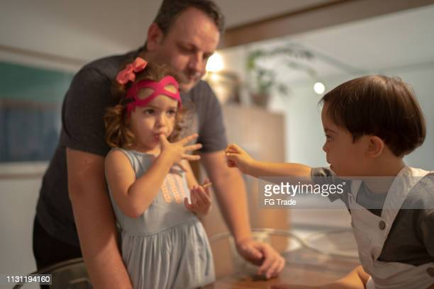 Family with twin sibling (Down Syndrome Boy and Girl) eating chocolate