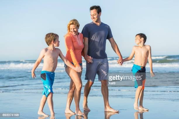 Famille avec deux garçons à pied sur la plage