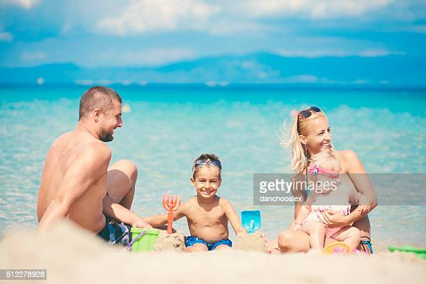 Family with two children at the beach playing