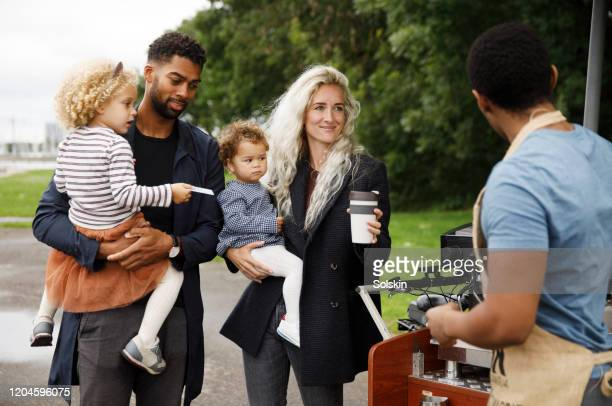 family with two children buying coffee at bicycle coffee shop - tvåbarnsfamilj bildbanksfoton och bilder