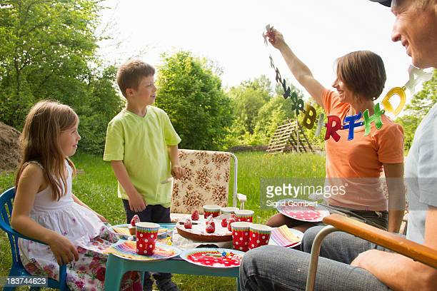 Family with two children celebrating birthday outdoors
