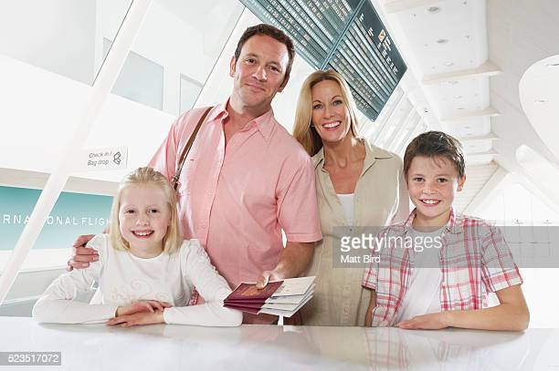 Family with two children (10-12, 13-15) checking in at airport desk