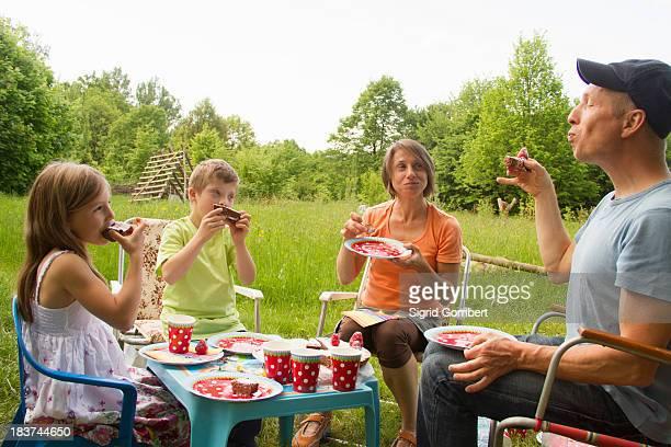 Family with two children enjoying birthday cake picnic