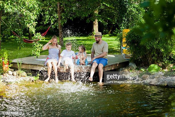 Family with two children having fun by the pond, Munich, Bavaria, Germany