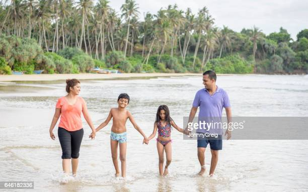 Family with two children holding hands on beach