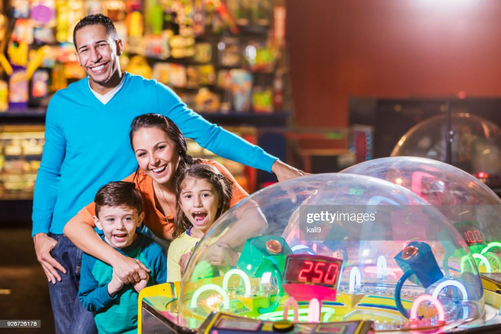 Family with two children in amusement arcade : Stock Photo