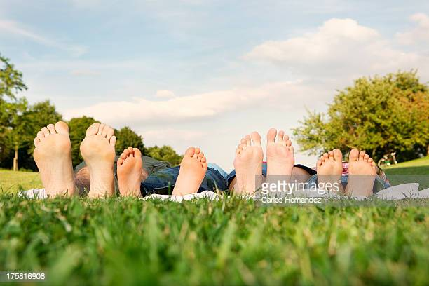 Family with two children lying on grass, focus on feet