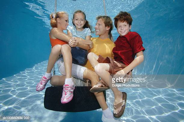 Family with two children (10-11) on tire swing underwater
