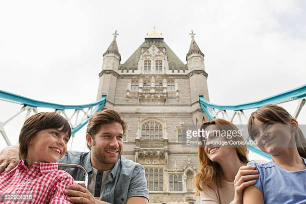 Family with two children (10-12) on tour bus with view of Tower Bridge in background, London, England, UK