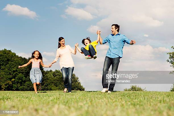 Family with two children, parents swinging boy