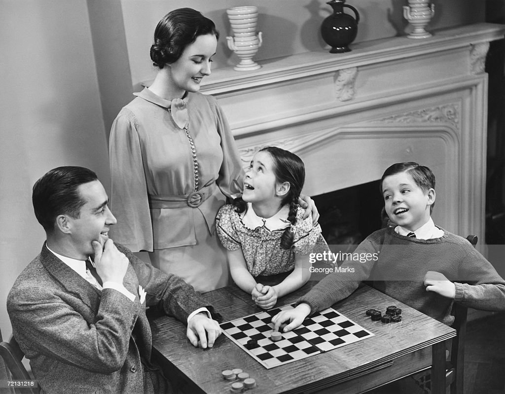 Family with two children (8-9) playing checkers (B&W), elevated view : Stock Photo