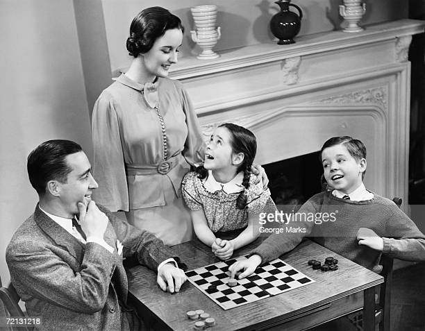 family with two children (8-9) playing checkers (b&w), elevated view - game board stock photos and pictures