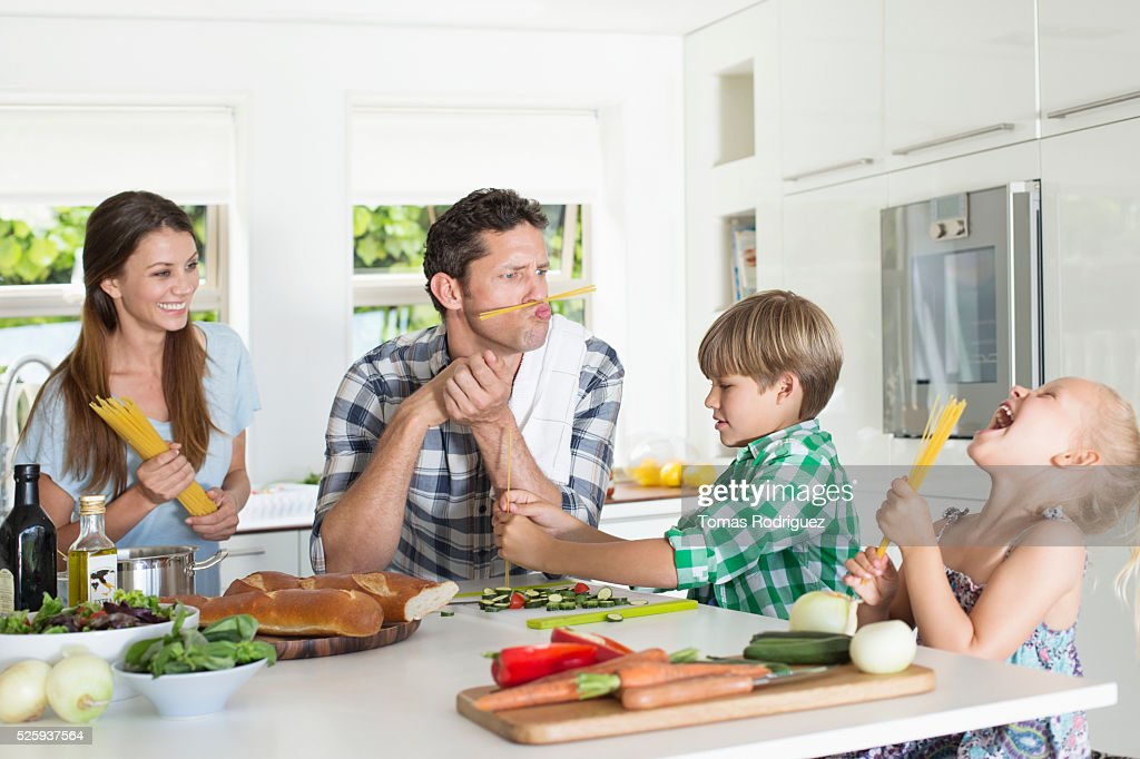 Family with two children (4-5 ,6-7) playing in kitchen : Stock Photo
