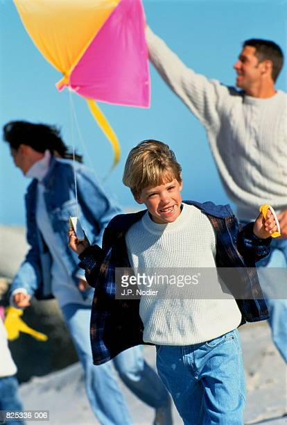 Family with two children (6-8) playing on beach, boy flying kite