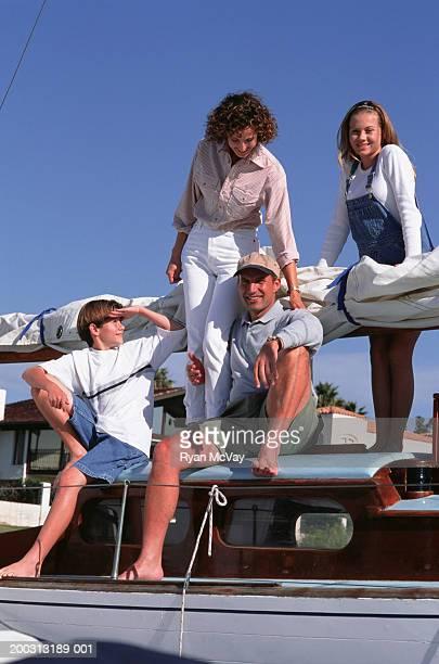 family with two children (10-11), (14-15), posing on boat, portrait - 10 11 jahre stock-fotos und bilder