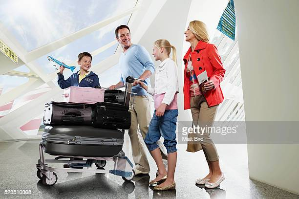 Family with two children (10-12, 13-15) pushing trolley through airport