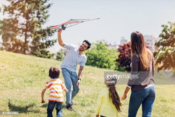 família com duas crianças soltando pipa - releasing - fotografias e filmes do acervo