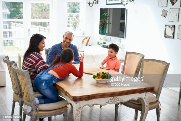family with two children sitting at dinner table and talking - filipino family dinner stock pictures, royalty-free photos & images