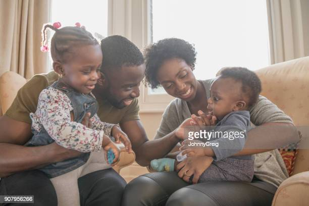family with two children sitting on armchairs at home - afro caribbean ethnicity stock pictures, royalty-free photos & images
