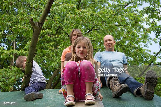 Family with two children sitting on playhouse roof
