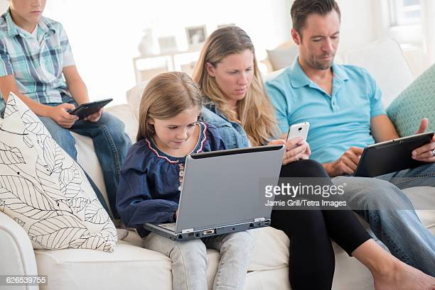Family with two children (6-7, 8-9) sitting on sofa, using laptop and digital tablets