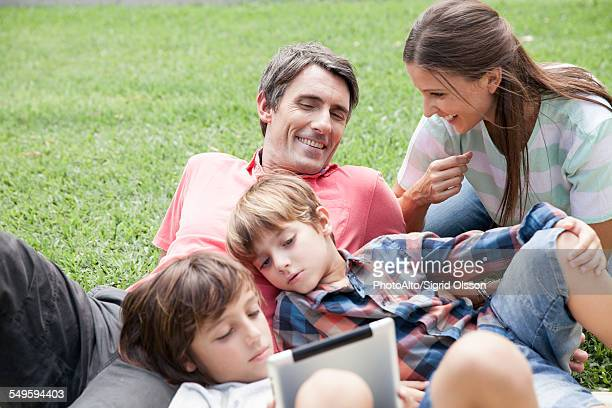 family with two children spending afternoon at park, young boys using digital tablet - free download photo stock photos and pictures