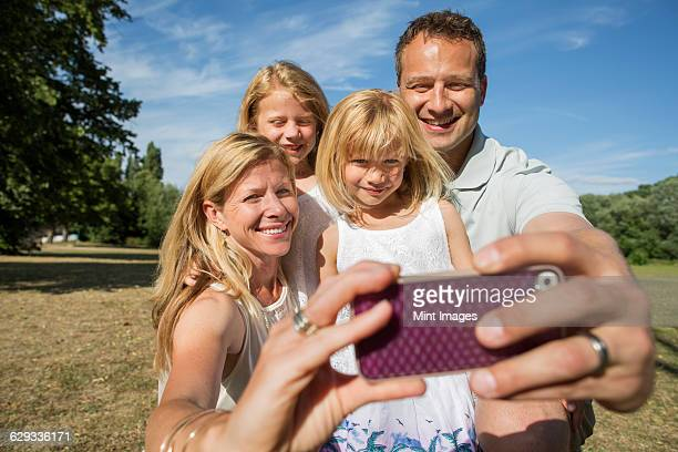 Family with two children, taking a selfie.
