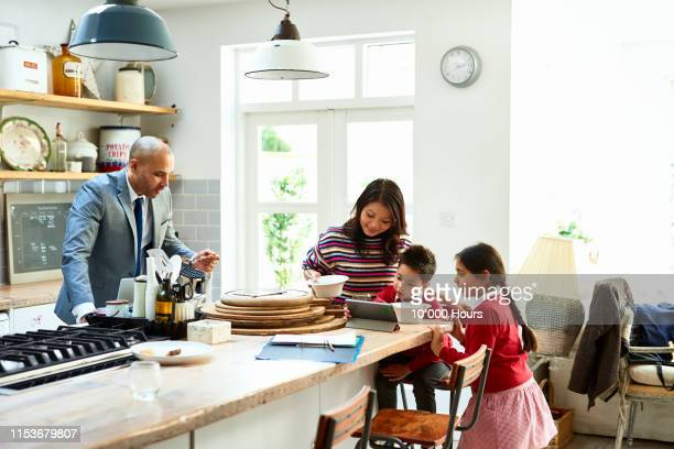 family with two children using tablet at home in kitchen - breakfast stock pictures, royalty-free photos & images