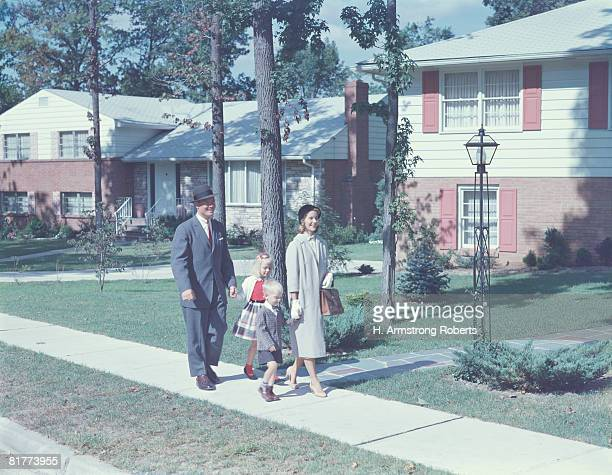Family with two children walking along suburban street. (Photo by H. Armstrong Roberts/Retrofile/Getty Images)