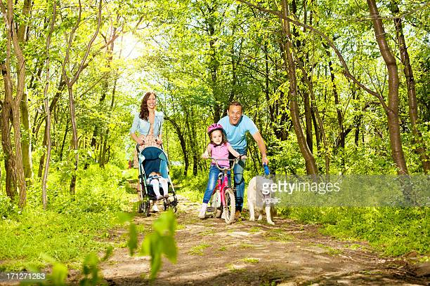 Family With Two Children Walking and cycling in a forest.