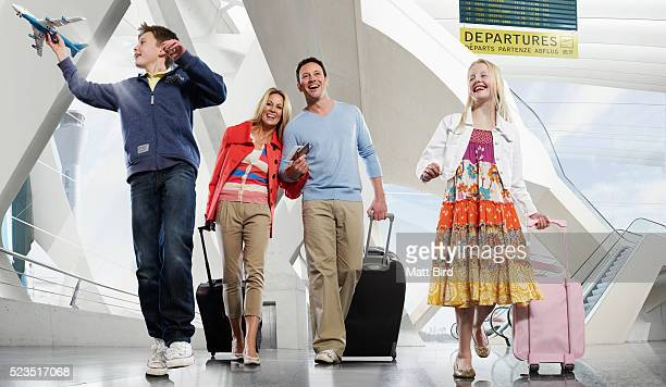 Family with two children (10-12, 13-15) walking through airport