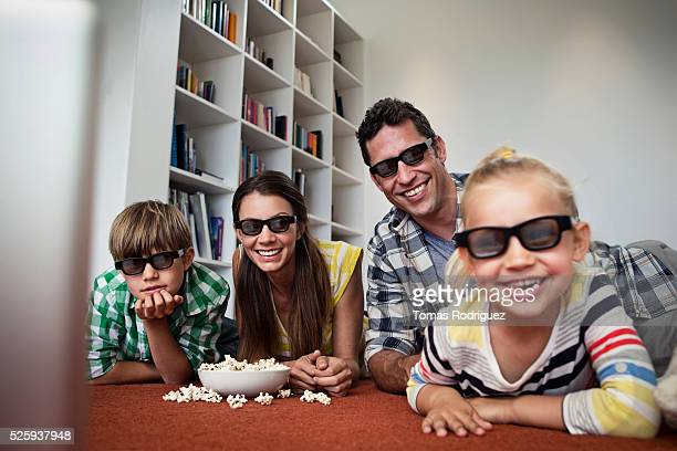 Family with two children (4-5 ,6-7) watching tv on floor