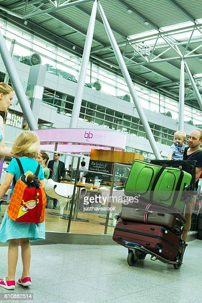 Family with two kids and luggage in airport