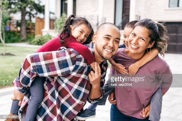 family with two kids looking at camera - mixed race person stock pictures, royalty-free photos & images