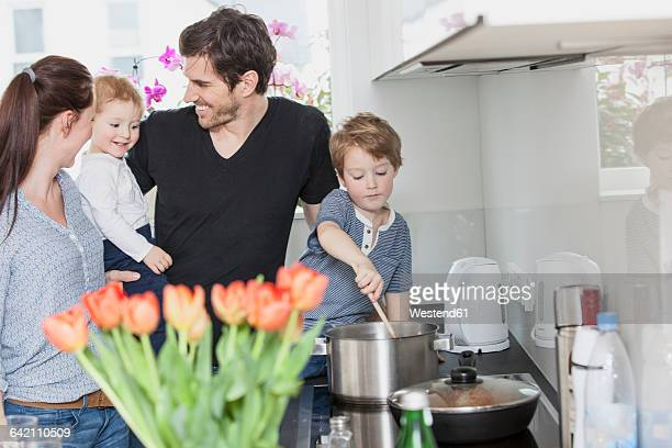 Family with two kids preparing food in kitchen