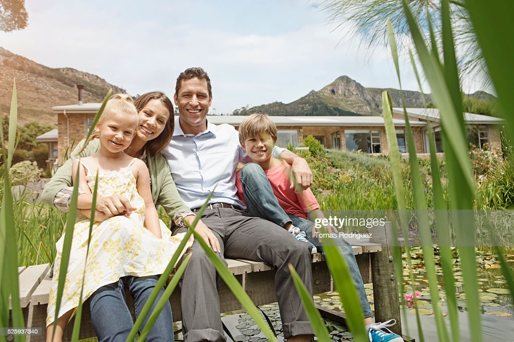 Family with two kids (4-5, 10-12) sitting on jetty : Stock Photo