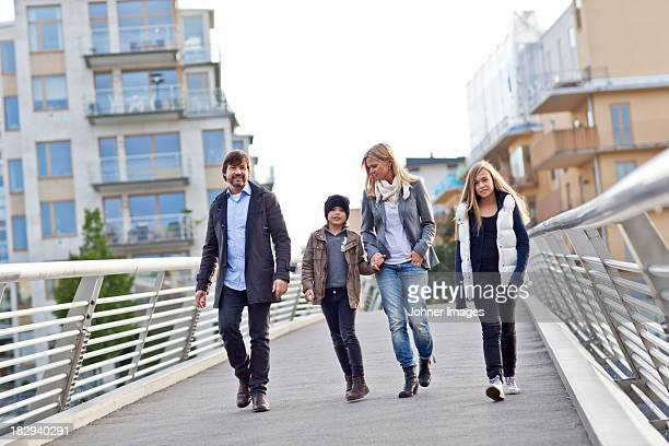 Family with two kids walking on footbridge