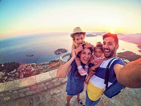 Family with two little daughters travel in nature, making selfie, smiling 873385094