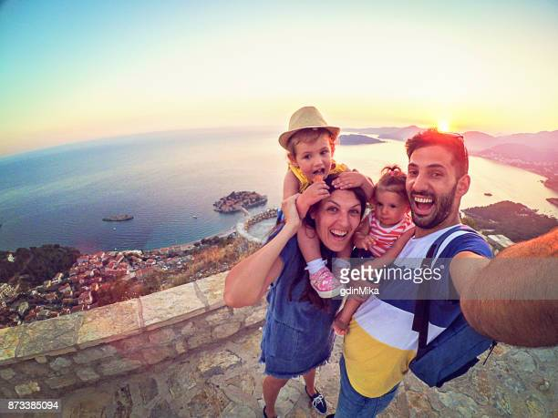 family with two little daughters travel in nature, making selfie, smiling - vacanze foto e immagini stock