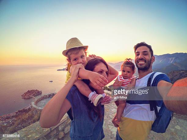 Family with two little daughters travel in nature, making selfie