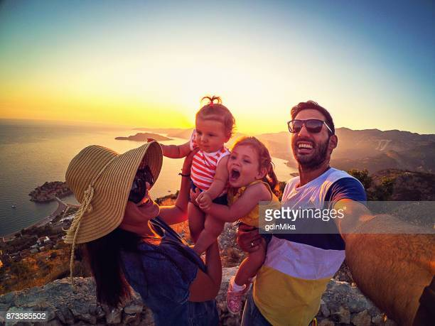 Family with two little daughters travel in nature, making selfie, smiling