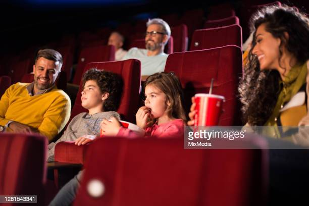 family with two little kids enjoying at the cinema - film premiere stock pictures, royalty-free photos & images