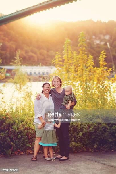Family with two moms standing in a park