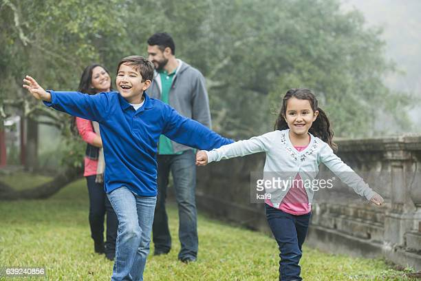 Family with two playful children taking a walk in park