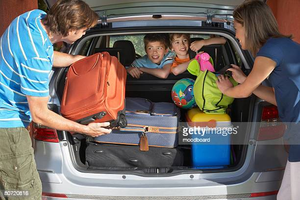 Family with two sons (6-11) loading car trunk with luggage