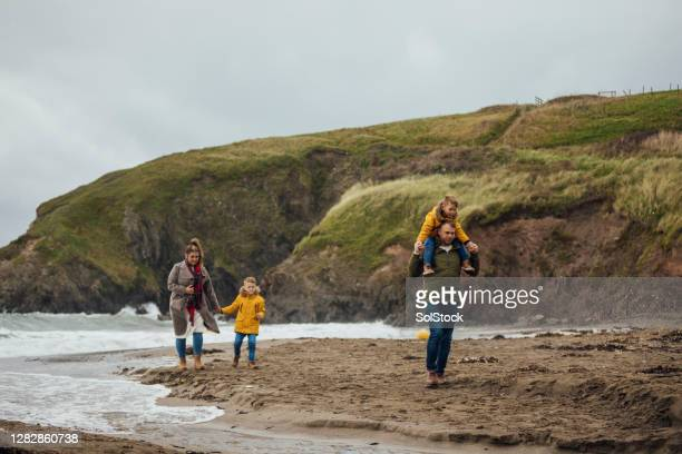 family with two young boys at the beach - weekend activities stock pictures, royalty-free photos & images