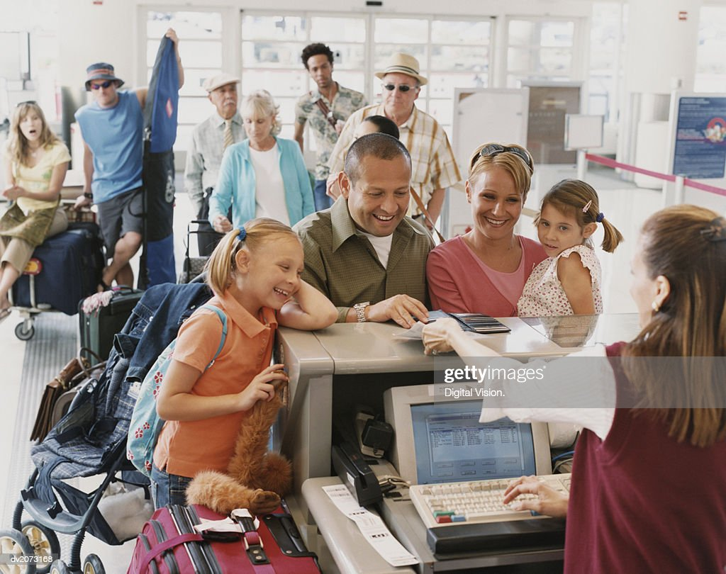 Family With Two Young Children Checks in at an Airport : Stock Photo