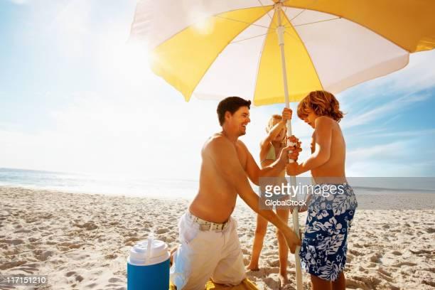 Familie mit Sonnenschirm am Strand an einem sonnigen Tag